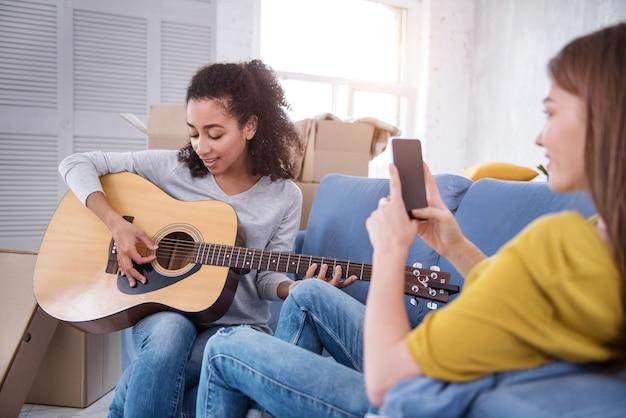 Песня для тебя. жизнерадостная кудрявая девушка играет на гитаре и посвящает песню своей соседке по комнате, пока снимает ее на телефон