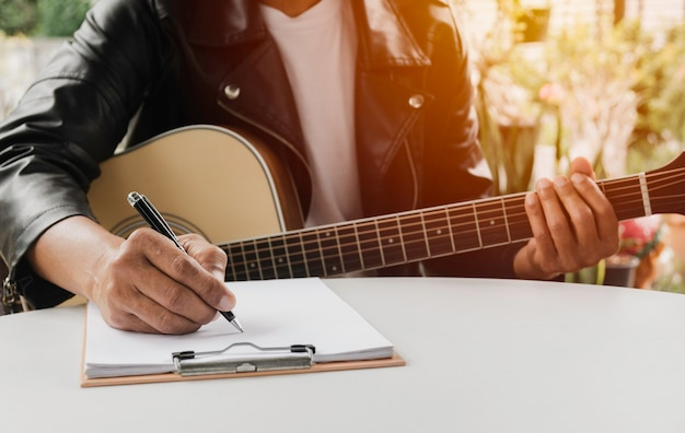 A song writer holding pen for compose a song. musician playing acoustic guitar. live music and abstract musical concept.