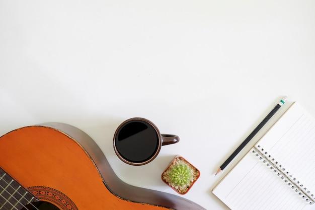 ソングライターは、ミュージシャンのアコースティックギターとメモ帳の紙とコーヒーカップのあるワークスペースを上面の机の上に置きます。