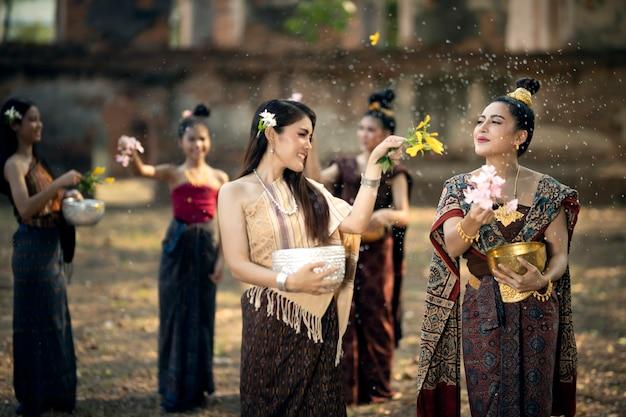 ソンクラン祭り。タイの民族衣装を着た女性が、タイの正月とされるタイの国民的伝統であるソンクラン祭りに水をかけています。
