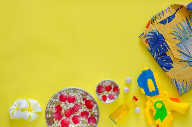 Songkran festival background with flowers and scented water to give blessing and accessories to play water