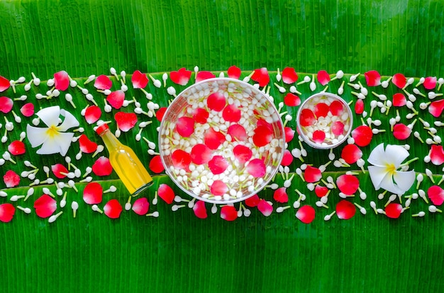 Songkran festival background with flowers in water bowls and scented water for blessing on wet banana
