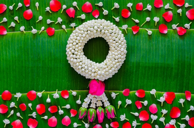 Songkran festival background with jasmine garland and flowers on banana leaf background.