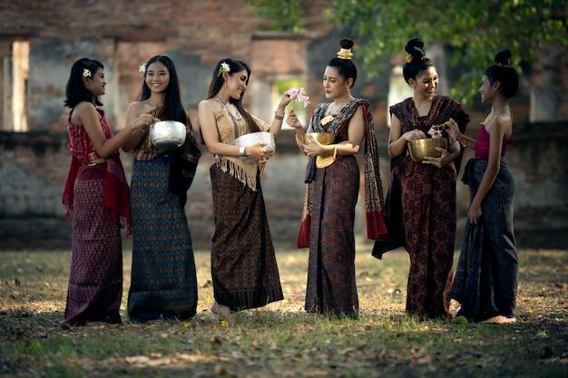 ソンクラン祭りタイの民族衣装を着た若い女性の多くがソンクランデーに水をかけています。