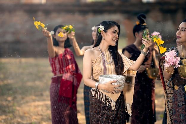 ソンクランフェスティバル少女は水をはねかけ、ソンクラーンデーと呼ばれるタイの新年の伝統に参加しています。