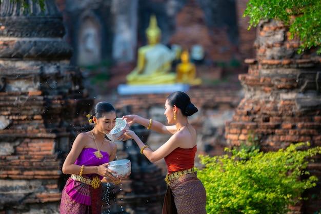 Тайские девушки в тайском традиционном платье брызг воды во время фестиваля songkran фестиваля, аюттхая, таиланд.