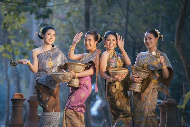 Красивая азиатская женщина брызгая воду во время фестиваля тайского, фестиваля songkran традиции.