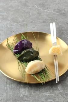 Сонпхён - это традиционная корейская еда, которую едят в новый год или в день корейской благодарности. подается на золотой корейской тарелке с палочками для еды. копировать пространство
