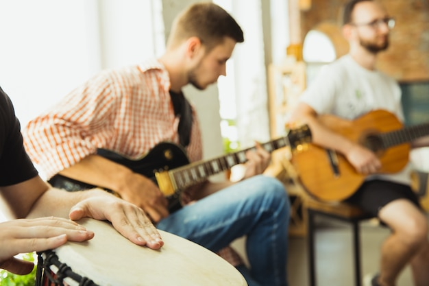 Songs. musician band jamming together in art workplace with instruments. caucasian men and women, musicians, playing and singing together. concept of music, hobby, emotions, art occupation.