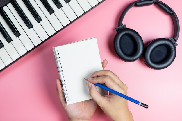 Songwriter is writing his new music on to a blank notebook