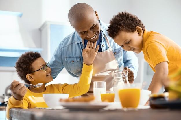 Сладкая привязанность. приятный маленький мальчик ласкает подбородок отца и нежно улыбается, подавая детям завтрак