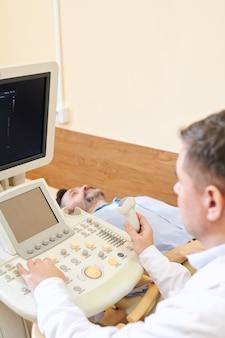 超音波検査機の画面を見て、患者を診察しながら臓器のサイズを分析する超音波検査者