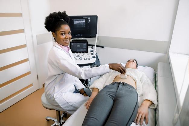 Молодая негритянка доктор sonographer используя машину ультразвука на работе