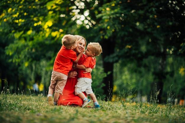 Сыновья обнимаются с матерью в парке