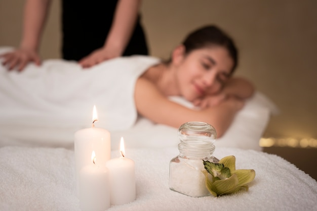 Soothing spa candles with defocused woman