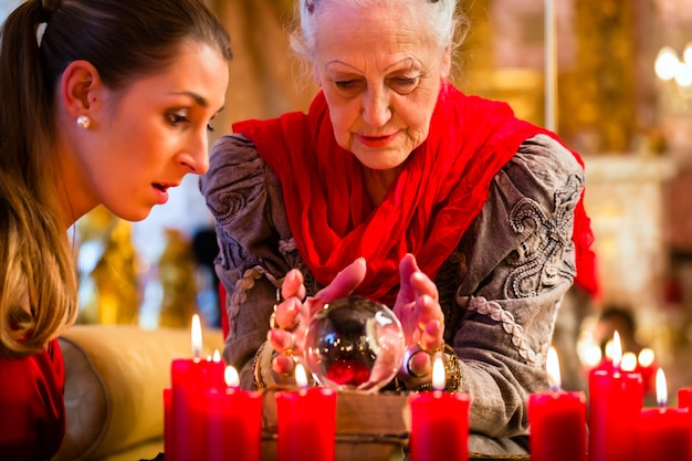 Soothsayer with crystal ball and client