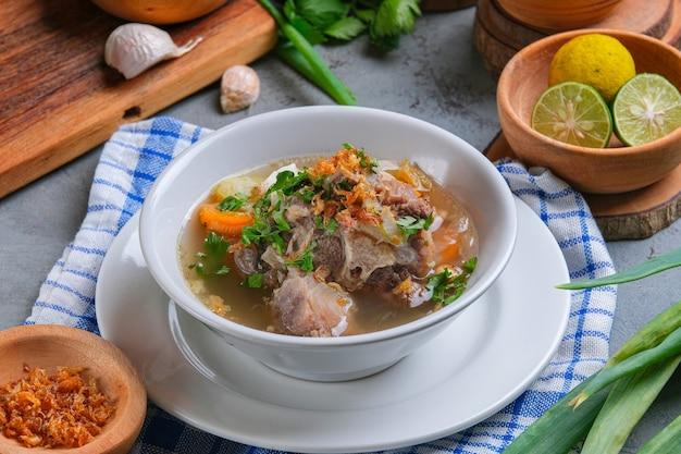 소프 분투트 또는 소꼬리 수프는 소박한 회색 배경의 흰색 그릇에 제공됩니다. 인도네시아 전통 요리