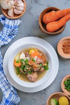 Sop buntut или суп из бычьего хвоста подают в белой миске на деревенском сером фоне. индонезийская традиционная кулинария