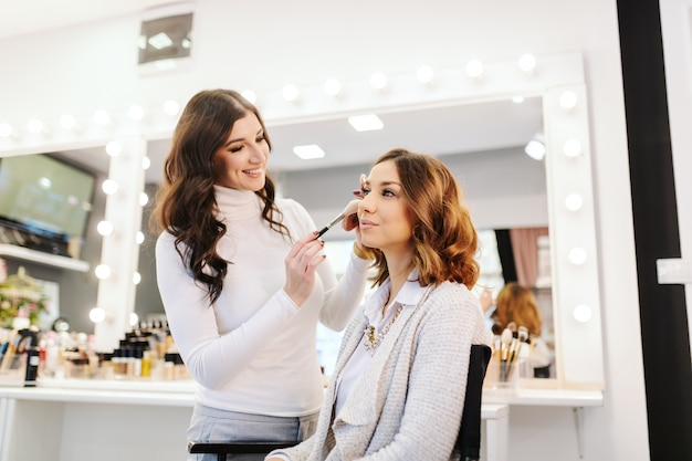 Sophisticated beautiful caucasian brunette sitting in beauty salon while makeup artist putting blush on woman's cheeks.