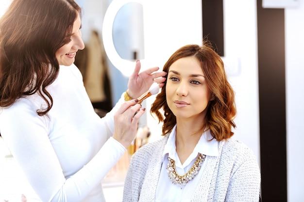 메이크업 아티스트가 여자의 뺨에 홍당무를 넣는 동안 미용실에 앉아 정교한 아름다운 백인 갈색 머리.