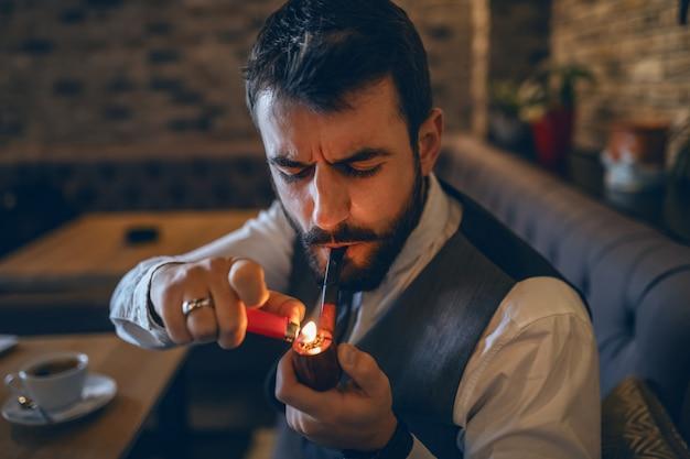 洗練された白人のひげを生やしたビジネスマンがカフェに座っている間パイプを照明します。