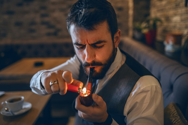 Sophisticated caucasian bearded businessman lighting a pipe while sitting in cafe.