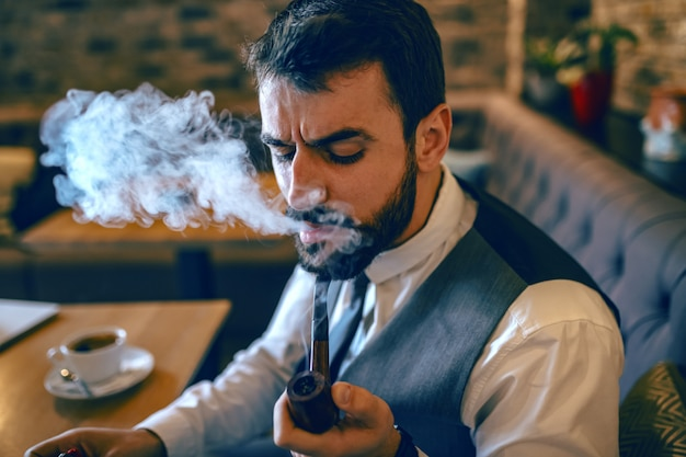 Sophisticated caucasian bearded businessman in suit sitting in cafe and smoking tobacco from pipe.