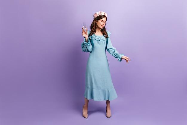 紫色の壁にシャンパングラスを楽しんでいる洗練されたヨーロッパの女性。青いドレスを着た黒髪モデルの全身写真。
