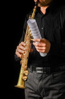 Сопрано-саксофон в руках на черном фоне