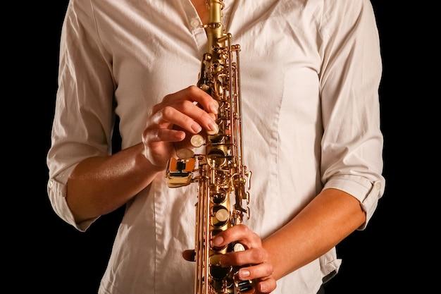 Сопрано-саксофон в руках девушки на черной поверхности