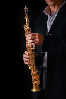 Сопрано-саксофон в руках парня на черной поверхности