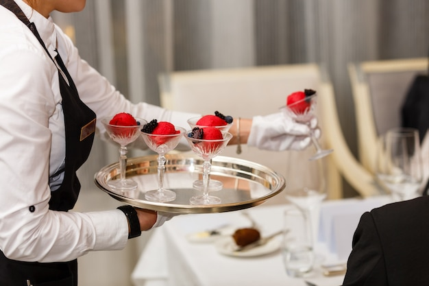 Sorbet cream, waiter is carrying desserts on a tray for summer
