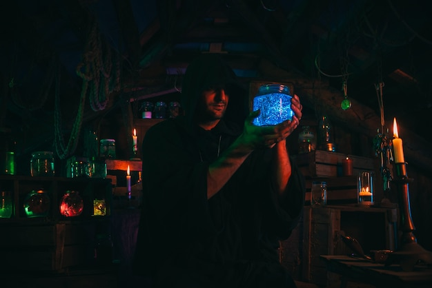 Sorcerer alchemist in dark clothes is engaged in potion making in a craft workshop with a colorful neon light