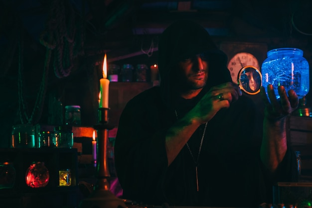 Sorcerer alchemist in dark clothes is engaged in potion making in a craft workshop