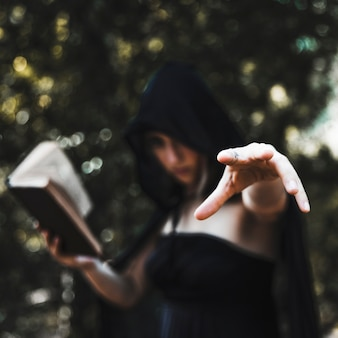 Sorceress casting spell in woods daytime
