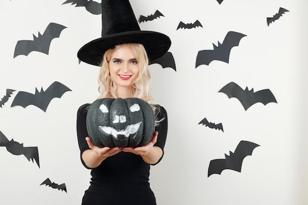Колдунья держит черную тыкву на хэллоуин
