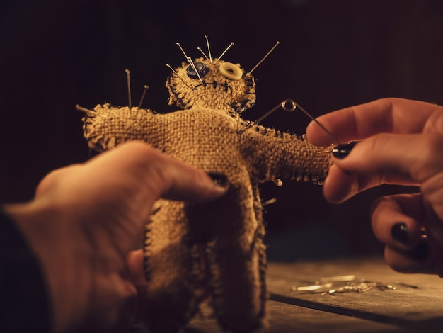 A sorceress pierces a voodoo doll with a pin, causing harm or damage to a person, closeup.