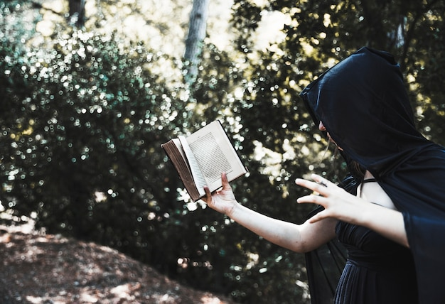 Sorceress using magic tome in sunny thicket