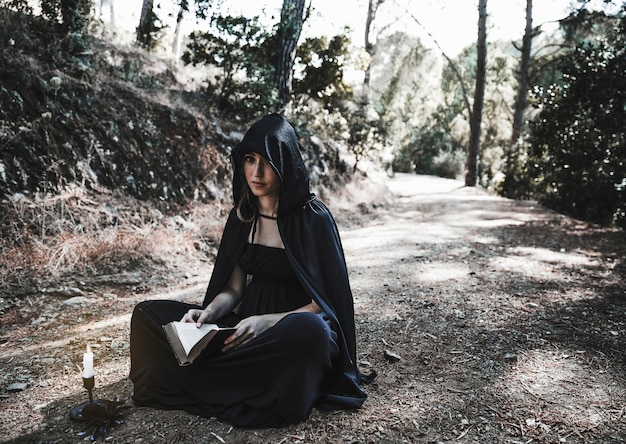 Sorceress with opened book and candlestick sitting on forest ground