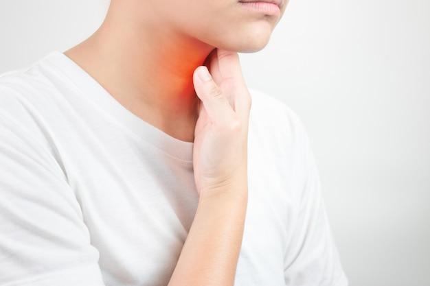 Больное горло. вызывается сухим воздухом без влаги. азиаты используют свои руки, чтобы коснуться шеи. здравоохранение и медицинские концепции