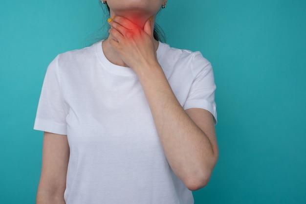 喉の痛み。彼女の病気の首に触れている美しい若い女性の手のクローズアップ。ヘルスケアと医療の概念。