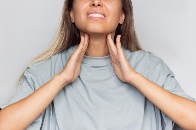 인후통 그녀의 목을 잡고 목 통증을 가진 젊은 백인 금발 여자의 자른 샷