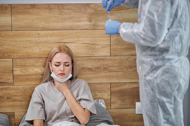 독감 코로나 바이러스 시즌에 인후염. 의사가 의료 검사를 준비하는 동안 집에서 침실에 앉아있는 동안 목을 만지고 통증을 느끼는 여성이 코로나 19 증상으로 고통 받고 있습니다.