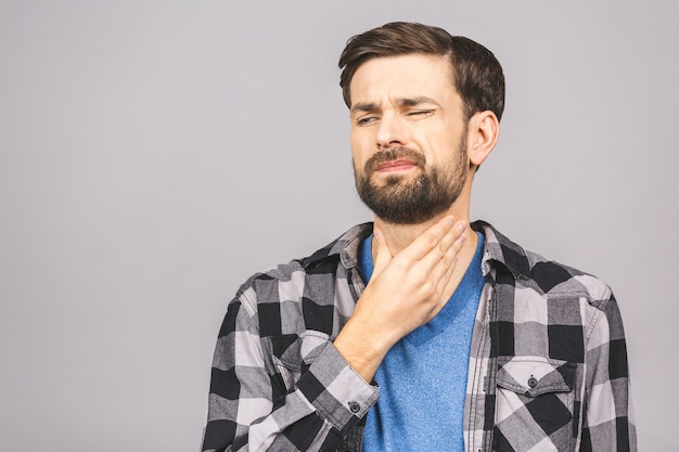 Sore throat. men touching the neck isolated against gray white wall.