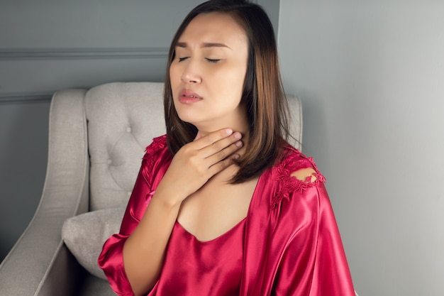 Sore throat pain symptoms. throat infection. a woman wearing a satin nightgown and red robe suffering from hoarseness or laryngitis in the living room at night.