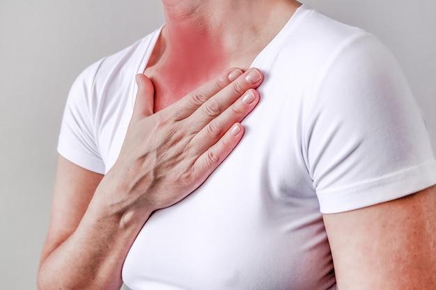 Боль в горле, показанная красным, держите руку, изолированную на белом фоне.