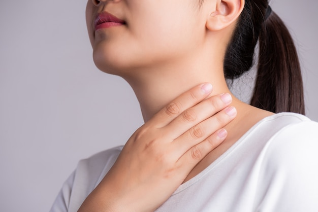喉の痛み。彼女の病気の首に触れる女性の手。医療コンセプト。