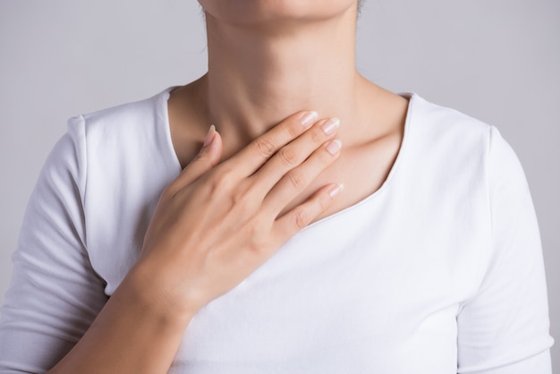 Sore throat. woman hand touching her ill neck. healthcare and medical.