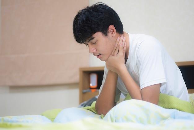 목 쓰림. 그의 아픈 목을 만지고 젊은 남자 손. 의료 및 의료 개념