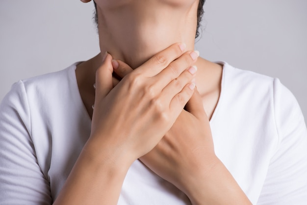 Sore throat. young woman hand touching her ill neck. healthcare concept.